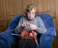 De oude vrouw zit in een leunstoel Royalty-vrije Stock Afbeelding