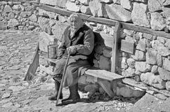 De oude vrouw zit langs steenmuur royalty-vrije stock foto's