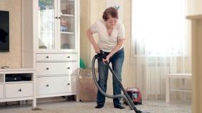 De oude vrouw zuigt de woonkamer, doet thuis het schoonmaken stock footage