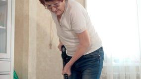 De oude vrouw zuigt de woonkamer, doet thuis het schoonmaken stock video