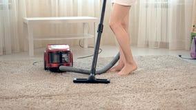 De oude vrouw zuigt de woonkamer, doet thuis het schoonmaken stock videobeelden
