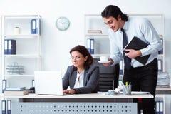 De oude vrouwelijke chef- en jonge mannelijke werknemer in het bureau stock afbeeldingen