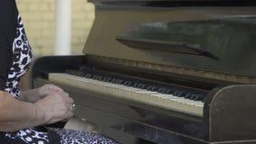 De oude vrouwen open dekking en begint de piano te spelen stock footage