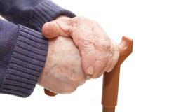 De oude vrouwenhand leunt op wandelstok Stock Afbeeldingen