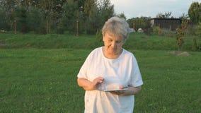 De oude vrouwenjaren '80 die een digitale tablet in openlucht houden stock footage