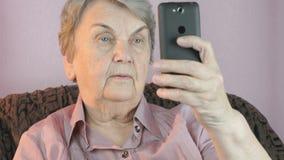De oude vrouwenjaren '80 die selfie gebruikend mobiele telefoon nemen stock video