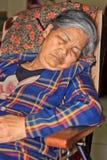 De oude vrouwenslaap op de zitkamerstoel stock fotografie