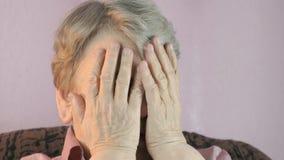 De oude vrouwenzitting behandelt binnen gezicht haar handen stock video