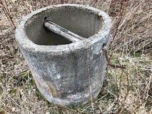 De oude wijnoogst verliet grijs die beton, cement diep goed met drinkwater in het bos wordt verbrijzeld royalty-vrije stock afbeeldingen