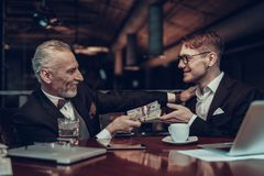 De oude Zakenman geeft geld aan de Jonge Mens royalty-vrije stock afbeelding