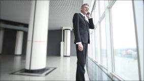 De oude zakenman spreekt op de telefoon dichtbij de panoramische vensters Mens die op een celtelefoon spreken met een ernstige bl stock videobeelden