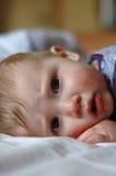 De oude zieke baby die van acht maanden in bed ligt stock foto