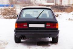 De oude, zwarte, Duitse achtermening van de familieauto in de winter Stock Fotografie