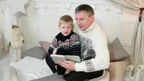 De ouder en een kind lezen een verhaal, vader en zijn kleine zoon die een boek lezen samen, familielezing thuis, een goed stock videobeelden