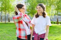De ouder en de tiener, moeder spreken met haar tienerdochter 13, 14 jaar oud Achtergrondaard, park Stock Afbeelding