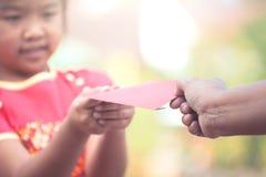 De ouder geeft geld in rode envelop aan weinig kindmeisje Royalty-vrije Stock Foto's