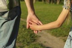 De ouder houdt de hand van een klein kind royalty-vrije stock fotografie