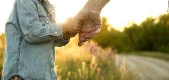 De ouder houdt de hand van een klein kind stock foto