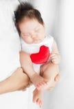 De ouder houdt/wiegen een leuke aanbiddelijke kindslaap in beschermende wapens, knuffelend met een rood muf hart Stock Afbeelding