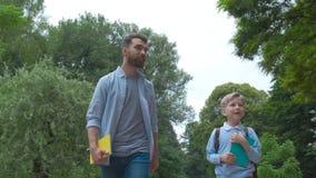 De ouder neemt kind aan school De leerling van lage school gaat studie in openlucht met rugzak De vader en de zoon gaan hand in h stock videobeelden