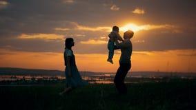 De ouder werpt zijn zoon in de lucht, een de zomeravond, zonsondergang stock footage