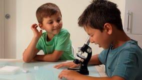 De oudere broer kijkt door een microscoop stock footage