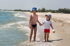 De oudere broer met zijn jongere broer bevindt zich op de handen van de kust gelukkige holding stock afbeelding