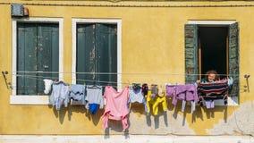 De oudere die vrouw inspecteert linnen het drogen op kabels buiten haar venster worden uitgerekt royalty-vrije stock afbeelding
