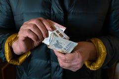 De oudere hogere vrouw houdt EURO bankbiljetten - Oosteuropees salarispensioen stock afbeeldingen
