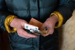De oudere hogere vrouw houdt EURO bankbiljetten - Oosteuropees salarispensioen royalty-vrije stock afbeelding