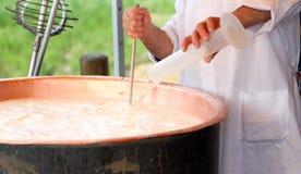 De oudere Kaasmaker giet melkstremsel in koperpot voor het maken che Stock Afbeelding