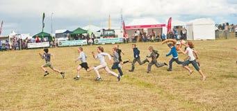 De oudere kinderen die in Nairn rennen tonen Stock Afbeeldingen