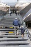De oudere mens en het kleine meisje beklimmen treden aan de centrale spoorweg van Utrecht Stock Afbeelding