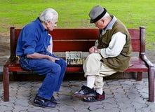 De oudere mensen spelen schaak op een bank Stock Foto