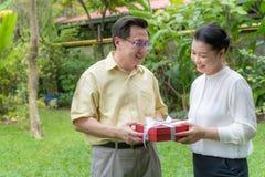 De oudere paren geven giften om liefde te tonen stock afbeeldingen