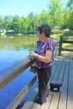 De oudere vrouw bekijkt vijver met draagbare zuurstofbuis stock foto's