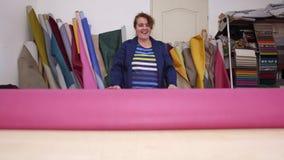 De oudere vrouw in een meubilairfabriek bereidt een roze materiaal voor het meten en het snijden voor stock footage