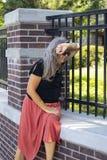De oudere vrouw met kleding en zonnebril en het lange grijze haar zitten door omheining buiten landgoed of park die op haar wapen Stock Fotografie