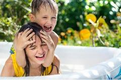 De oudere zuster en de jongere broer stellen in een opblaasbare pool in de tuin tevreden, Royalty-vrije Stock Fotografie