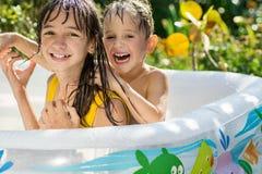 De oudere zuster en de jongere broer stellen in een opblaasbare pool in de tuin tevreden, Royalty-vrije Stock Afbeeldingen