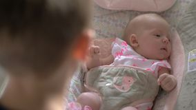 De oudere zuster van de broer lulling baby aan slaap in schommelstoel stock footage