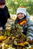 De oudere zuster verzamelt een stapel van bladeren, en haar jongere broer helpt haar Stock Foto's