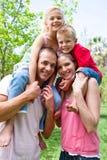 De ouders die hun kinderen geven vervoeren per kangoeroewagen rit Stock Foto's