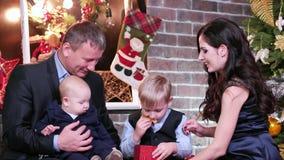 De ouders en de kinderen brengen tijd samen, moedervader en zonen door die Kerstmis op giften letten, familie die nieuw jaar vier stock footage