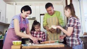 De ouders en de jonge zusters hebben grote tijd en bereiden maaltijd voor stock footage
