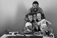 De ouders en de kinderen hebben gezichten met gouache, exemplaarruimte worden geschilderd die Kunst en ambachtconcept De kunstena Royalty-vrije Stock Afbeeldingen