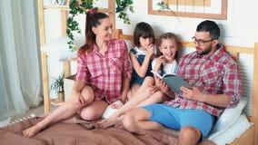 De ouders en twee dochters liggen in bed en de papa leest boek aan hen, langzame motie stock footage