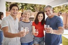 De ouders en de volwassen kinderen heffen glazen aan camera in tuin op royalty-vrije stock foto's