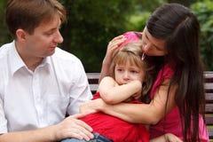 De ouders kalmeren schreeuwend meisje op gang in de zomertuin Stock Afbeelding