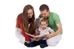 De ouders kijken boek met zoon Royalty-vrije Stock Foto's
